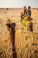 First person view riding a camel with another camel with two people riding it in front. Thar desert camel treking, Rajasthan, India.