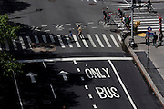 Seen from the roof of a Federal building, an aerial view of people crossing Broadway in New York City.
