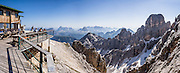 """From Rifugio Guido Lorenzi on Monte Cristallo in the Ampezzo Dolomites, look northeast across blue ridges of the Sesto Dolomites (Dolomiti di Sesto, or Sexten/Sextner/Sextener Dolomiten) to the pyramids of Tre Cime di Lavaredo (Italian for """"Three Peaks of Lavaredo,"""" called Drei Zinnen or """"Three Merlons"""" in German). A lift to Forcella Staunies on Monte Cristallo gives unforgettable views over the Dolomites mountains (part of the Southern Limestone Alps) near Cortina d'Ampezzo, in the Province of Belluno, Veneto region, Italy, Europe. Monte Cristallo lies within Parco Naturale delle Dolomiti d'Ampezzo. Directions: From Cortina, drive 6km east on SR48 to the large parking lot for Ski Area Faloria Cristallo Mietres (just west of Passo Tre Croci Federavecchia). Take a chair-lift from Rio Gere to Son Forca (rising from 1698m to 2215m). Then take the old style ovovia (egg-shaped) Gondellift Forcella Staunies to Rifugio Guido Lorenzi (2932m) for astounding views. Climbers enjoy spectacular via ferrata routes here. Cortina gained worldwide fame after hosting the 1956 Winter Olympics. UNESCO honored the Dolomites as a natural World Heritage Site in 2009. This panorama was stitched from 8 overlapping photos."""