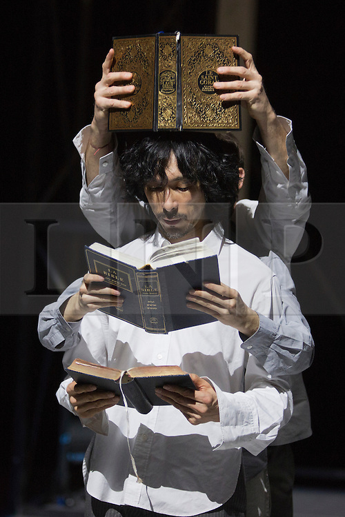 "© Licensed to London News Pictures. 24/01/2014. London, England. Pictured: Yasuyuki Shuto with Koran and Bible. Belgian dancer/choreographer Sidi Larbi Cherkaoui's work ""Apocrifu"" uses the language of the body to explore apocryphal religious texts, accompanied by the polyphonic singing from the all-male Corsican vocal ensemble ""A Filetta"". Dancers: Sidi Larbi Cherkaoui, Dimitri Jourde and Yasuyuki Shuto. Performances at the Queen Elizabeth Hall, Southbank Centre from 24th to 25the January 2014. Photo credit: Bettina Strenske/LNP"