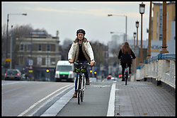 A lady Cyclist riding a bike over Wandsworth Bridge, South West London, United Kingdom. Friday, 13th December 2013. Picture by Andrew Parsons / i-Images