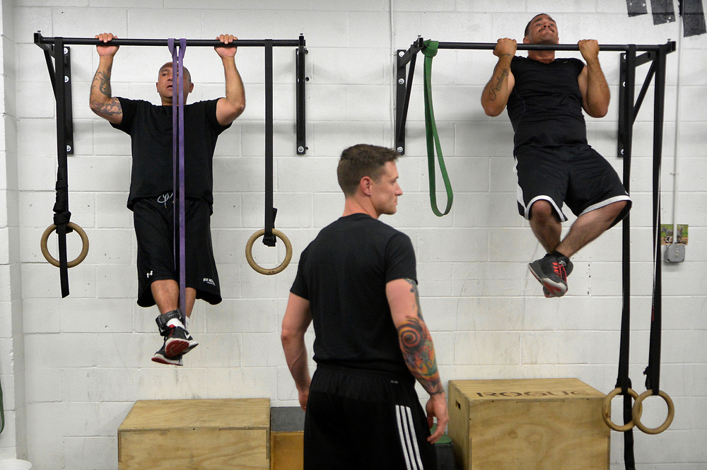 gbs090717l/ASEC -- Jason Garcia, left, and Leroy Sanchez, right, do pull-ups under eye of trainer Barry Ore during the Addicts2Athlete fitness/therapy program for recovering addicts on Thursday, September 7, 2017. (Greg Sorber/Albuquerque Journal)