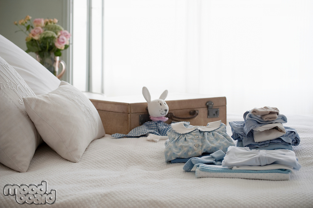 Childrens clothes folded on bed next to suitcase
