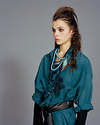 Young woman posing in a blue shirt dress with hair in fishtail braid.