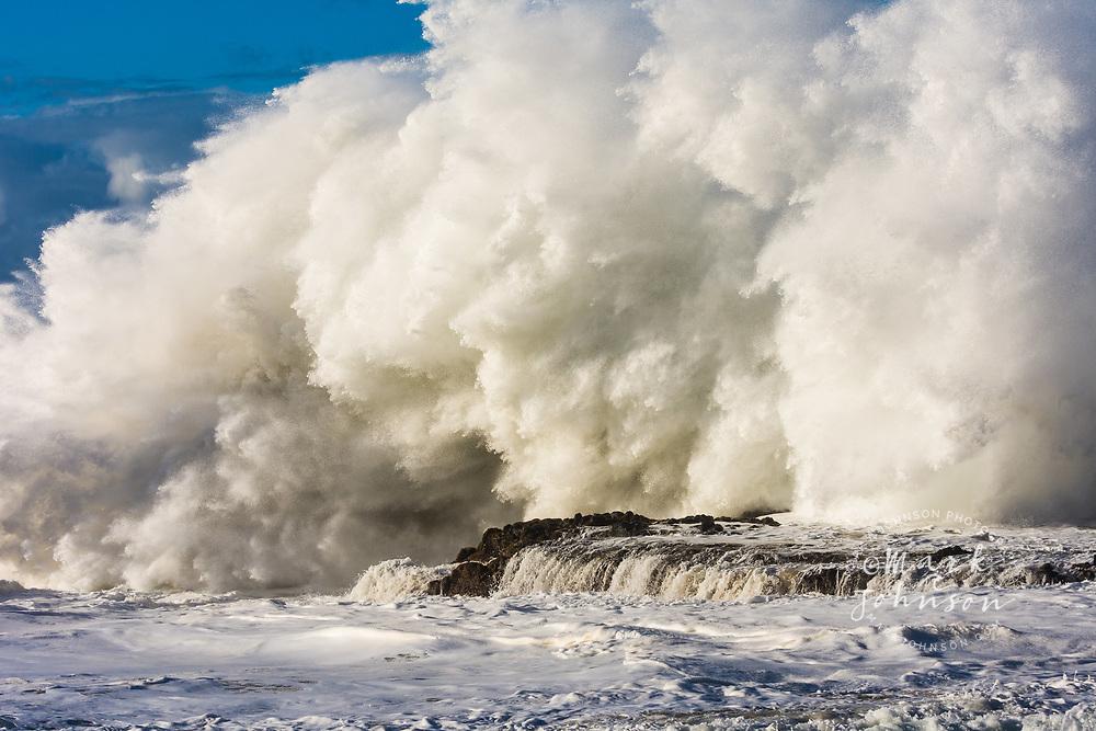 Huge shorebreak wave breaking onto the rocks off Kauai, Hawaii