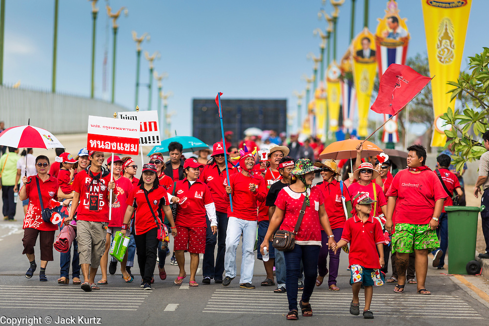 17 MAY 2014 - BANGKOK, THAILAND:  Red Shirt supporters walk down Aksa Road to a Red Shirt rally in Bangkok. Thousands of Thai Red Shirts, members of the United Front for Democracy Against Dictatorship (UDD), members of the ruling Pheu Thai party and supporters of the government of ousted Prime Minister Yingluck Shinawatra are rallying on Aksa Road in the Bangkok suburbs. The government was ousted by a court ruling earlier in the week that deposed Yingluck because the judges said she acted unconstitutionally in a personnel matter early in her administration. Thailand now has no functioning government. Red Shirt leaders said at the rally Saturday that any attempt to impose an unelected government on Thailand could spark a civil war. This is the third consecutive popularly elected UDD supported government ousted by the courts in less than 10 years.   PHOTO BY JACK KURTZ