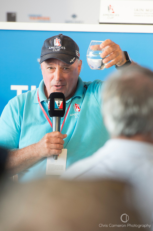 "America's Cup Village, Bermuda, 24th June 2017. Race director Ian Murray holds up a glass of water ""The closest thing I have to a crystal ball"" in response to a question on the weather at the morning media briefing ahead of day three of the America's Cup."