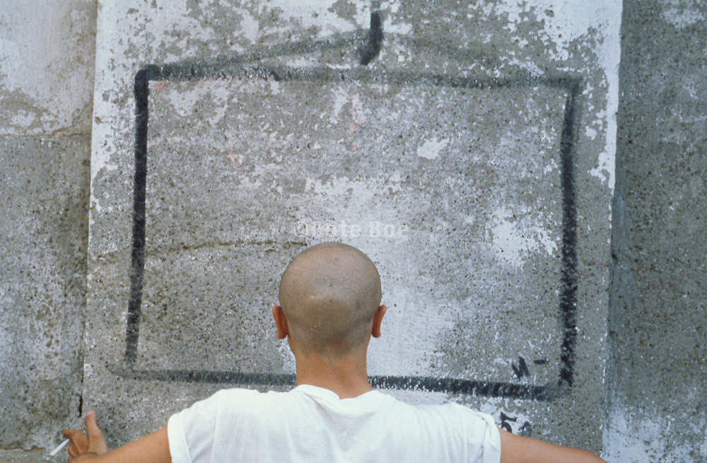back of man?s head and shoulders facing a concrete wall