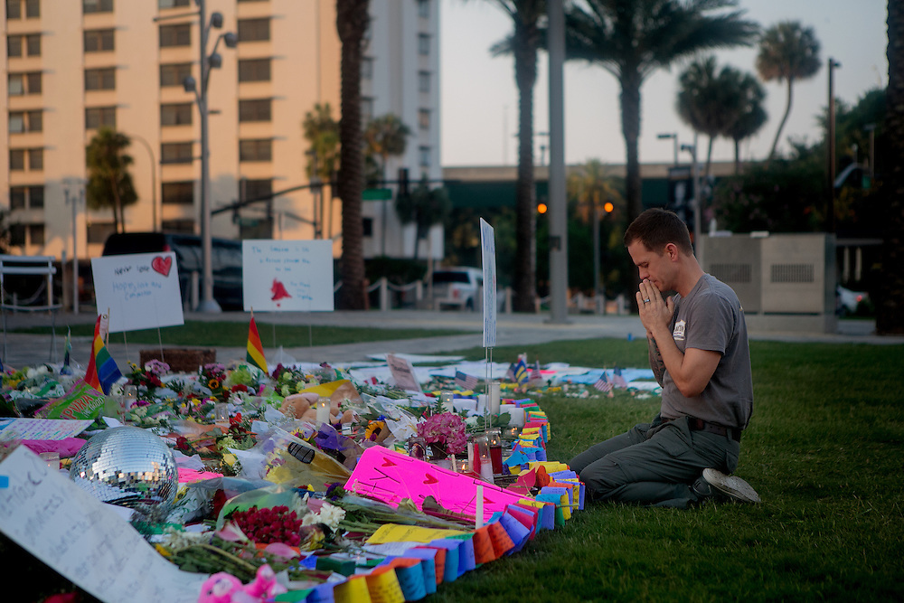 ORLANDO - JUNE 14, 2016: Matt Mitchell prays at a memorial outside the Dr. P. Phillips Center for the Performing Arts in memory of the victims of the Pulse nightclub in Orlando, Florida. CREDIT: Sam Hodgson for The New York Times.