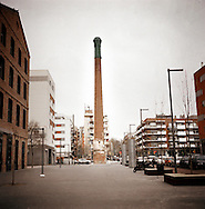 Poble Nou, Barcelona..An old chimney, the only part left of an old textile factory that was demolished, as a monument at the middle of a square in Poble Nou neighborhood , the working class residential area of Barcelona.