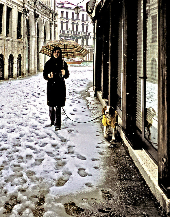 Young woman wearing boots and a winter coat, carrying an umbrella, walks her dog along a snowy calle in Venice.  The dog wears a coat, too.