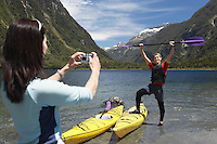Woman taking picture of man hoisting oar of kayak over head on shore of mountain lake