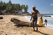 A man carries a stone anchor up the beach after freediving for mussels from wooden canoe just off shore, near Kovalam. Mussels sell for a high price in the markets to seafood restaurants frequented by tourists, fuelling this dangerous and harsh method of earning a living.