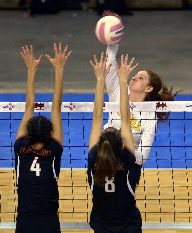 gbs110917a/SPORTS -- Cibola's Lauren Montoya hits against Eldorado's Catessa Duran, 4, and Micah Livesay, 8, during the State Volleyball Championships at the Santa Ana Star Center on Thursday, November 9, 2017. (Greg Sorber/Albuquerque Journal)