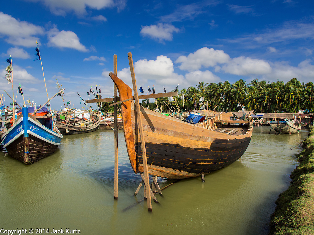 07 NOVEMBER 2014 - SITTWE, RAKHINE, MYANMAR: A partially finished boat in port in an IDP camp near Sittwe. The government of Myanmar has forced more than 140,000 Rohingya Muslims who used to live in Sittwe, Myanmar, into squalid Internal Displaced Person (IDP) camps. The forced relocation took place in 2012 after sectarian violence devastated Rohingya communities in Sittwe and left hundreds dead. None of the camps have electricity and some have been denied access to regular rations for nine months. Conditions for the Rohingya in the camps have fueled an exodus of Rohingya refugees to Malaysia and Thailand. Tens of thousands have put to sea in rickety boats hoping to land in Malaysia but sometimes landing in Thailand. The exodus has fueled the boat building boom on the waterfront near the camps. Authorities expect the pace of refugees fleeing Myanmar to accelerate during the cool season, December through February, when there are fewer storms in the Andaman Sea and Bay of Bengal.   PHOTO BY JACK KURTZ