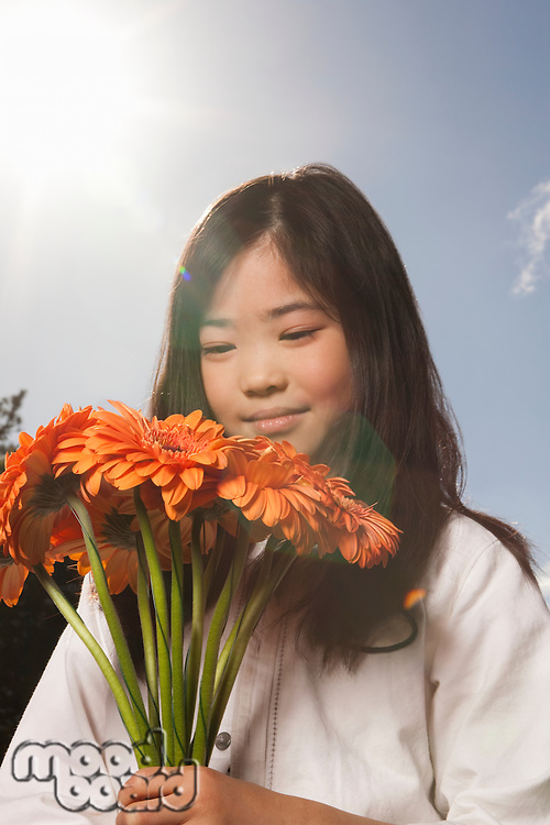 Asian girl holding bunch of flowers