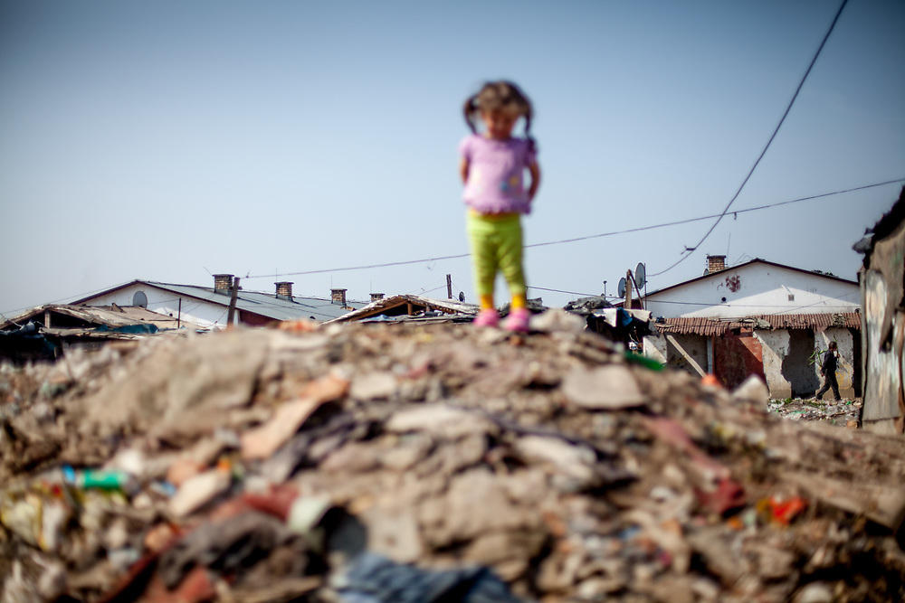 "A girl living at the Roma settlement ""Budulovska Street"" standing on a little hill. From about 800 inhabitants of the segregated settlement 'Budulovska Street' (2014) are roughly 392 children up to the age of 16 years."