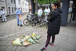 © Licensed to London News Pictures. 08/03/2019. Fulham, London, UK. A woman looks at flowers left at Lanfrey Place where 17yr old Ayub Hassan died of stab wounds sustained in an attack yesterday afternoon. Four teenagers have been arrested in connection with the murder, the investigation continues. Photo credit: Guilhem Baker/LNP