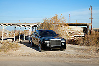 Rolls Royce parked on roadside in front of abandoned house