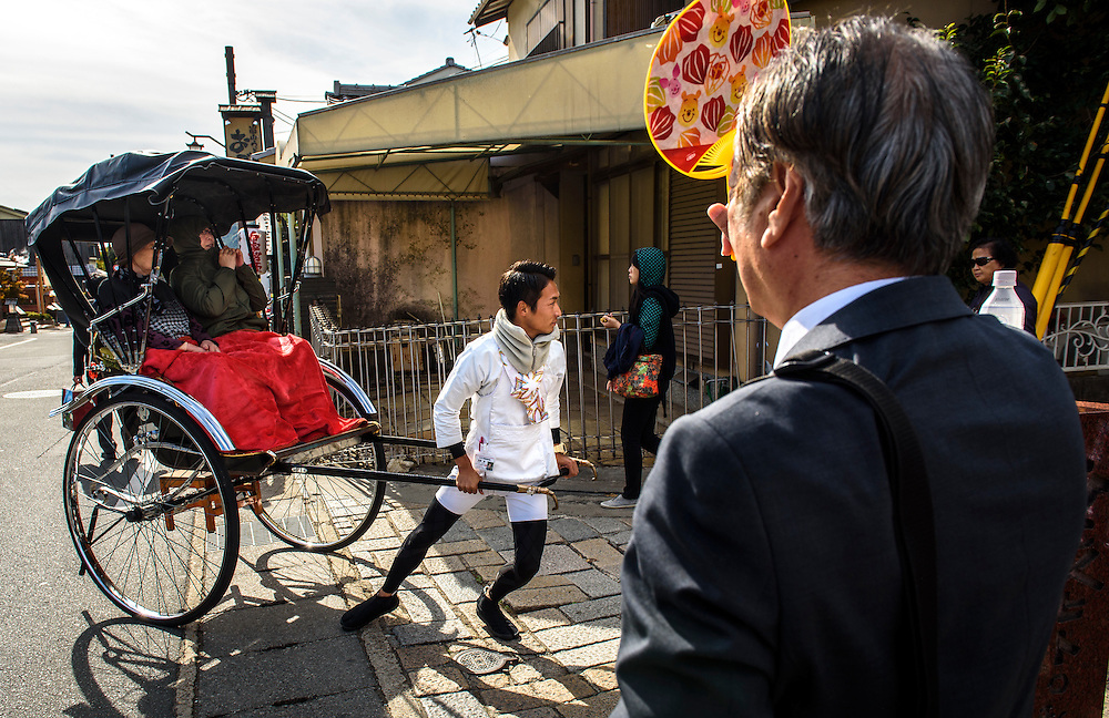 A rickshaw driver pulls tourists at Arashiyama, Kyoto, Japan.