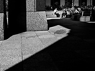 Office workers enjoying their lunch amid the shadows of midtown skyscrapers at 52nd st. and Sixth Avenue.