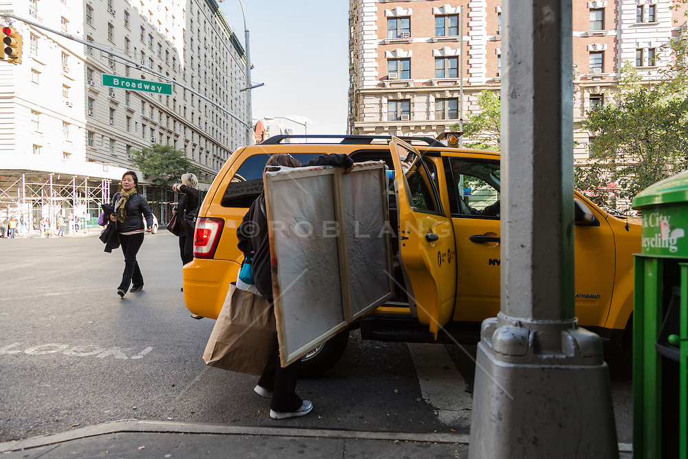 woman putting a large canvas into a taxi cab in New York City