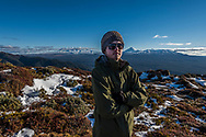 Matthew on the tops of Kaimanawa ranges with Volcanic plateau in the background.