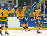 Lake Superior State Laker's Zach Trotman (4) and Will Acton (center) skate towards team captain Rick Schofield (right) as he celebrates scoring Saturday night during round one of the CCHA playoffs at Taffy Abel Arena.