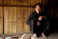 Burma/Myanmar. Akha man sitting near his house.
