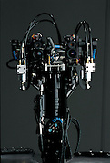 """DB gazes intently at the camera by means of two pairs of lenses in each """"eye."""" In a configuration increasingly common in humanoid robots, one lens in each pair sharply focuses on the center of the visual field while the other gives a broader perspective. These two points of view, surprisingly, mimic the human eye, which seamlessly blends together information from the fovea centralis, a small area of precise focus in the center of the retina, and the parafovea, a larger, but much less acute area surrounding the fovea. Similarly, DB has a vestibular system in its ears, vestibular systems being the inner-ear mechanisms that people use to balance themselves.  The DB project is funded by the Exploratory Research for Advanced Technology (ERATO) Humanoid Project and led by independent researcher Mitsuo Kawato. Based at a research facility 30 miles outside of Kyoto, Japan."""
