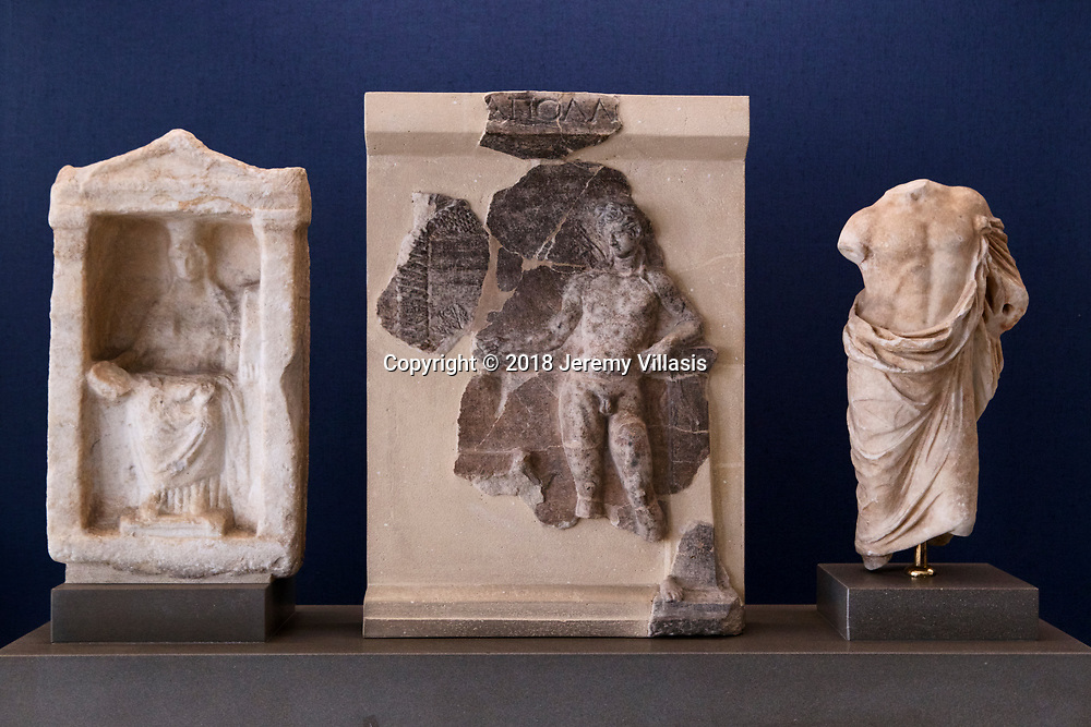 From left to right: Marble votive of the goddess Cybele enthroned (3rd century BC); fragment of a marble votive relief with representation of Apollo Delios, probably from Attica (late 2nd century BC); and marble torso of a statuette of Asklepios (late Hellenistic Period).