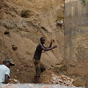 Local men work in the construction of a dam to prevent the erosion of the support pillars of a bridge in  central Bujumbura, Burundi.