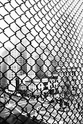 A foggy view of downtown San Francisco through a chain link fence.