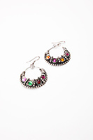 Colorful gems on earrings over white background