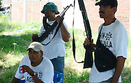 Aguililla's self-defense forces in the town of Pizandaro gather to battle the brutal Knights Templar drug cartel. Locals who had been operating independently in their own towns are increasingly working together. Though well-armed, some of their armor is improvised: the man in the center wears an upside down bowl stuffed with newspaper on his head.