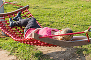 Young woman rests on a hammock in a garden