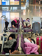 14 AUGUST 2013 - HONG KONG: People waiting to fly out of Hong Kong sleep in Terminal 2 at Hong Kong International Airport. Dozens of flights were delayed at one of the busiest airports in Asia and Hong Kong raised their alert to level 8, the highest, and closed schools and many businesses because of Severe Typhoon Utor. The storm passed within 260 kilometers of Hong Kong before making landfall in mainland China. Severe Typhoon Utor (known in the Philippines as Typhoon Labuyo) is an active tropical cyclone located over the South China Sea. The eleventh named storm and second typhoon of the 2013 typhoon season, Utor formed from a tropical depression on August 8. The depression was upgraded to Tropical Storm Utor the following day, and to typhoon intensity just a few hours afterwards. The Philippines, which bore the brunt of the storm, reported 1 dead in a mudslide and 23 fishermen missing at sea.     PHOTO BY JACK KURTZ