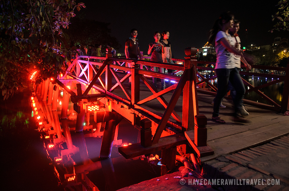 Visitors walk across The Huc Bridge (Morning Sunlight Bridge) at night. The red-painted, wooden bridge joins the northern shore of the lake with Jade Island and the Temple of the Jade Mountain (Ngoc Son Temple).
