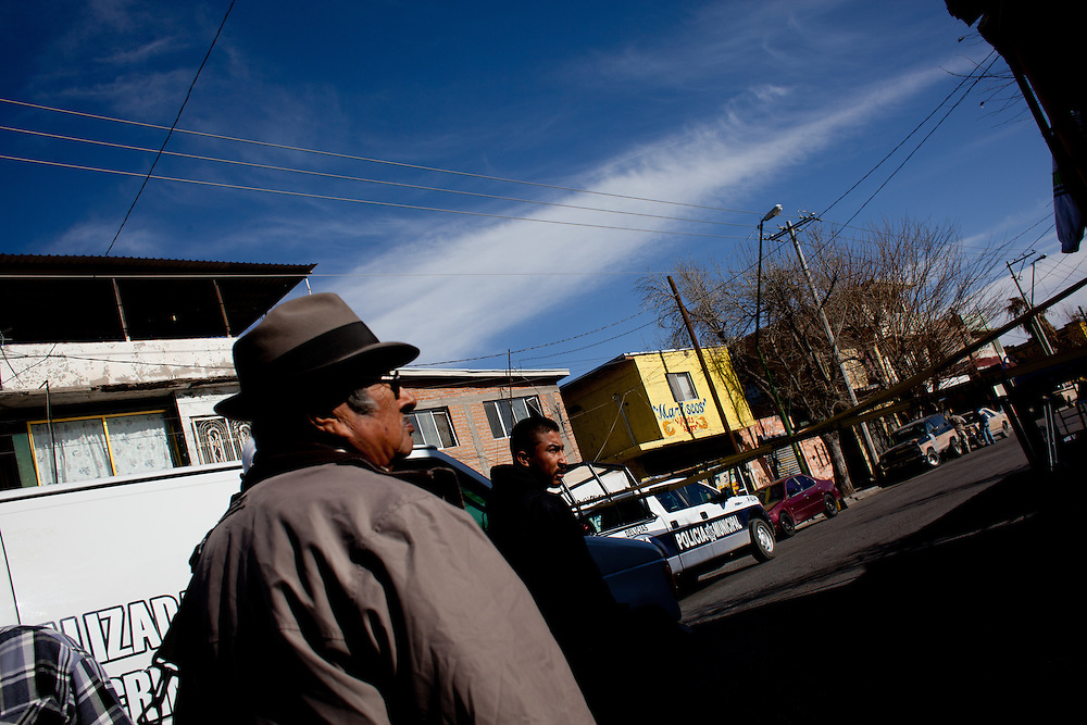 Bystanders watch police work a crime scene in Ciudad Juarez.