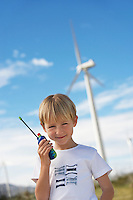 Boy (7-9) holding toy walky-talky at wind farm, portrait