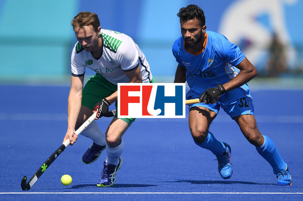 India's Chandanda Thimmaiah (R) and Ireland's Michael Darling fight for the ball during the men's field hockey India vs Ireland match of the Rio 2016 Olympics Games at the Olympic Hockey Centre in Rio de Janeiro on August, 6 2016. / AFP / MANAN VATSYAYANA        (Photo credit should read MANAN VATSYAYANA/AFP/Getty Images)