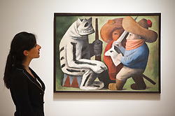 """Mexico: A Revolution in Art opens at the Royal Academy of Arts.<br /> A employee stands next to work by Jose Chavez Morado entitled """"Carnaval en Huejotzingo 1939"""" at the exhibition """"Mexico: A Revolution in Art, 1910 - 1940"""" which opens at the Royal Academy of Arts on the 6th of July. The show features over 120 paintings and photographs and examines the intense period of artistic creativity that took place in Mexico at the beginning of the 20th century,<br /> London, United Kingdom,<br /> Tuesday, 2nd July 2013<br /> Picture by Piero Cruciatti / i-Images"""