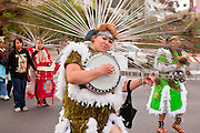"03 DECEMBER 2011 - PHOENIX, AZ:    A woman dances and plays banjo during a procession to honor the Virgin of Guadalupe in Phoenix Saturday. The Phoenix diocese of the Roman Catholic Church held its Sixth Annual Honor Your Mother Day Saturday to honor the Virgin of Guadalupe. According to Mexican Catholic tradition, on December 9, 1531 Juan Diego, an indigenous peasant, had a vision of a young woman while he was on a hill in the Tepeyac desert, near Mexico City. The woman told him to build a church exactly on the spot where they were standing. He told the local bishop, who asked for some proof. He went back and had the vision again. He told the lady that the bishop wanted proof, and she said ""Bring the roses behind you."" Turning to look, he found a rose bush growing behind him. He cut the roses, placed them in his poncho and returned to the bishop, saying he had brought proof. When he opened his poncho, instead of roses, there was an image of the young lady in the vision. The Virgin is now honored on Dec 12 in Catholic churches throughout Latin America and in Hispanic communitied in the US. PHOTO BY JACK KURTZ"