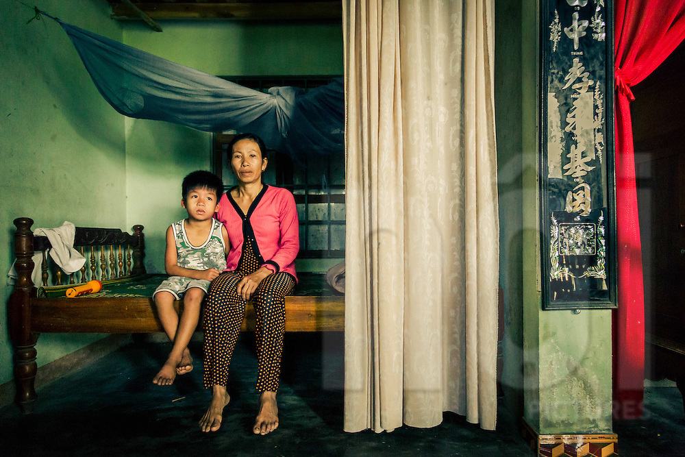 Portrait of a Vietnamese boy and his mother, a widow who's husband died in UXO accident, Quang Tri province, Vietnam, Southeast Asia