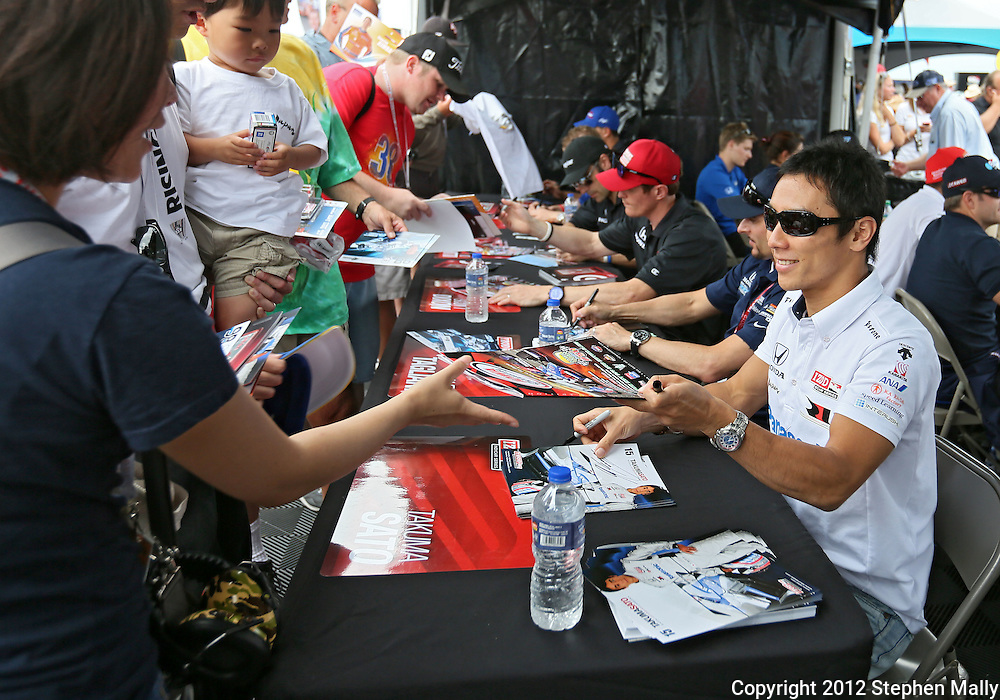 Takuma Sato signs autographs before the start of the IZOD IndyCar Iowa Corn Indy 250 auto race at the Iowa Speedway in Newton, Iowa on Saturday, June 23, 2012.