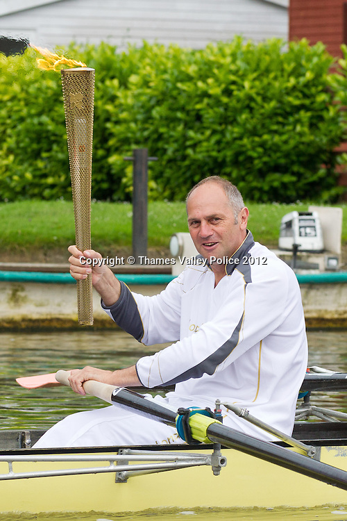 Henley, UNITED KINGDOM. July 10 2012.The Olympic Torch is rowed along the River Thames by Sir Steve Redgrave. Henley , Oxon.<br /> Photo Credit: Mark Chappell/TVP<br /> &copy; Thames Valley Police 2012. All Rights Reserved. See instructions.