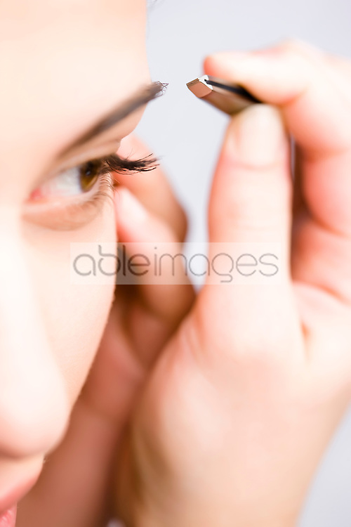 Extreme close up of a woman plucking her eyebrow with tweezers