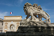 Stone lion sculpture and the Arc de Triomphe in Montpellier, south of France.