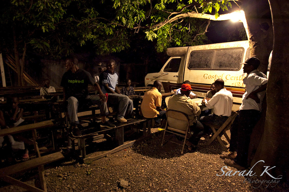 Haitian men from the local villages in the mountains of Bayonnais gather to pass time and play dominos on the campus of the International Christian Development Mission, Inc., an organization focusing on development work in the rural community of Bayonnais.