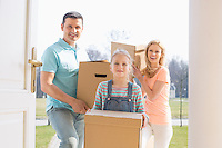 Happy family with cardboard boxes entering new home